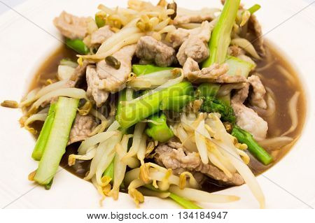 Pork fried bean sprouts and asparagus cooking