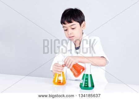 Asian boy doing science experiment with color liquid path of science education