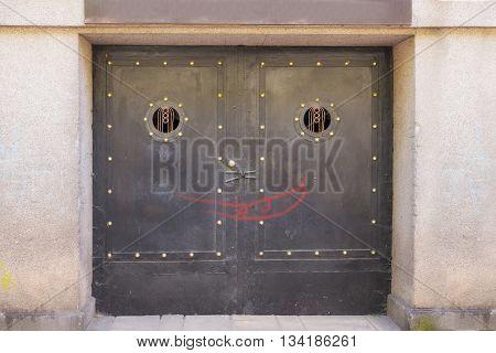 Old black metallic door with graffiti smile symbol