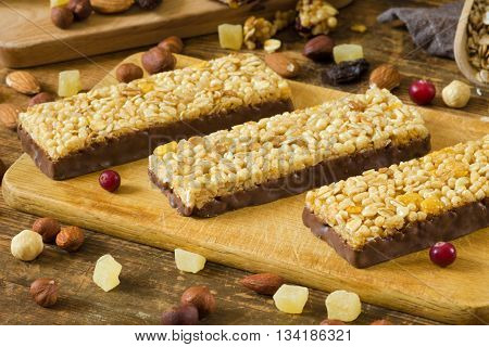 Granola bars with cornflakes, puffed cereals and rolled oats covered in chocolate on wooden cutting board