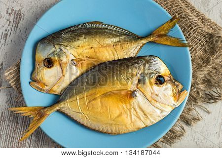 Two smoked fish on a blue plate on a light wooden background.