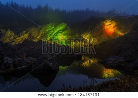 rocks with trees and water in mist and evening