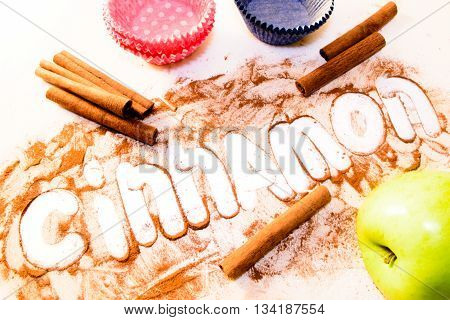 word cinnamon written on a white table with cinnamon