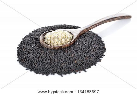dried black and white sesame with wooden spoon on white background