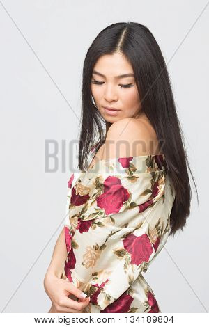 Portrait of fashion asian lady in spring dress demonstrating her shoulder to camera in studio. Beautiful brunette lady looking down.