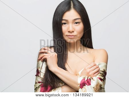 Portrait of beautiful fashion asian lady in summer dress in studio. Pretty lady posing with her arms crossed or folded isolated on grey background.