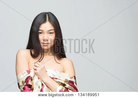 Portrait of pretty fashion asian lady in summer dress looking at camera. Beautiful lady with black hair posing in studio. Nude shoulders concept.