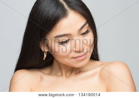 Closeup picture of cheerful asian nude lady in studio. Beautiful woman with black hair showing her beautiful shoulders isolated on grey.