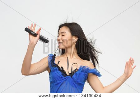 Attractive brunette holding microphone in front of her over white background. Fashion asian model in blue lingerie singing songs in studio.