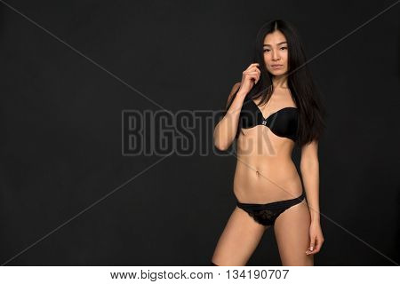 Beautiful lady wearing black underwear. Beauty photo shot, retouched image. Attractive asian sexy fashion model with natural hair, full lips, perfect skin posing in studio.