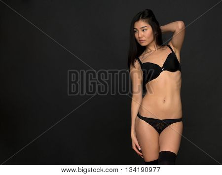 Portrait of fashion asian model in black lingerie in studio. Brunette lady looking away and touching her gorgeous hair.
