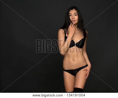 Attractive fashion asian model in lingerie or underwear posing in studio. Brunette woman in black underwear touching her natural hair.
