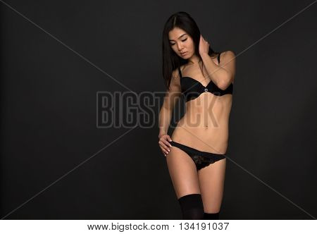 Picture of attractive and gorgeous woman looking down over grey background. Brunette fashion asian model in black lingerie or underwear in studio.