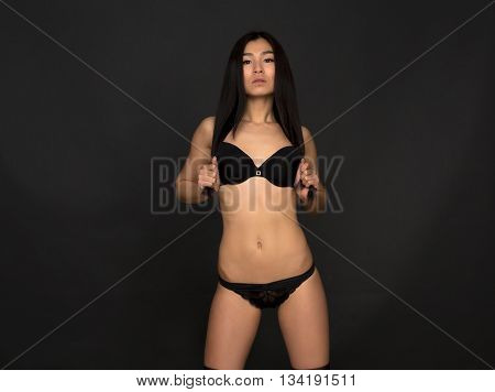 Portrait of beautiful woman looking at camera. Attractive fashion asian model in black lingerie or underwear touching her gorgeous hair in studio.