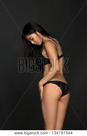 Portrait of fashion asian model in black lingerie or underwear posing over grey background in studio. Beautiful woman demonstrating her back.