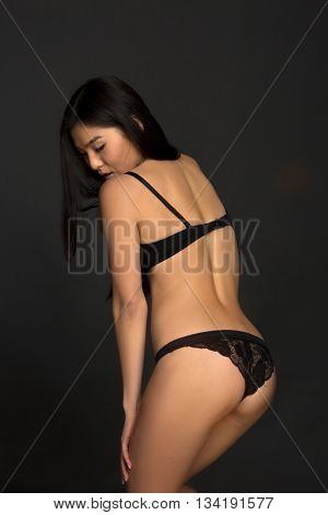 Portrait of beautiful woman demonstrating her back. Attractive fashion asian model in black lingerie or underwear posing over grey background in studio.
