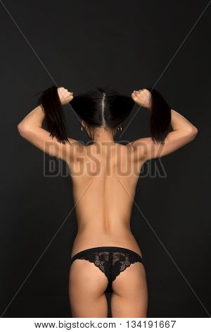 Topless fashion asian model touching her hair and posing in black lingerie or underwear in studio. Brunette lady showing her muscles.