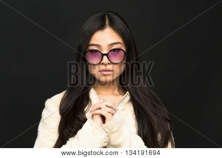 Portrait of fashion asian model woman in sunglasses in studio. Brunette lady posing for fashion magazine..