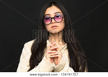 Portrait of fashion asian model woman in sunglasses in studio. Brunette woman clasped her hands in front of her over black background.