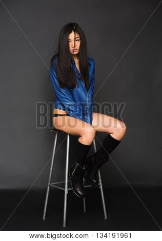 Portrait of fashion asian model in lingerie and blue jacket sitting on chair in studio. Sexy lady posing for photographer over grey background.