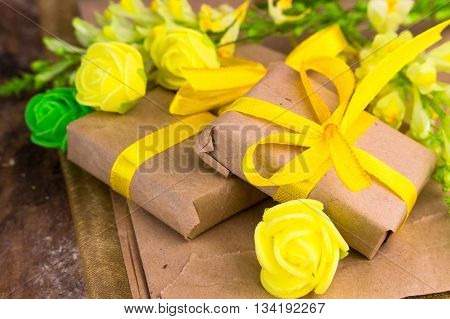 Yellow gift box wrapped in natural paper on wooden table top view