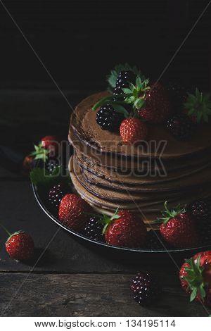 Chocolate pancakes in rusty pan with organic fruits like strawberries and blackberries vertical