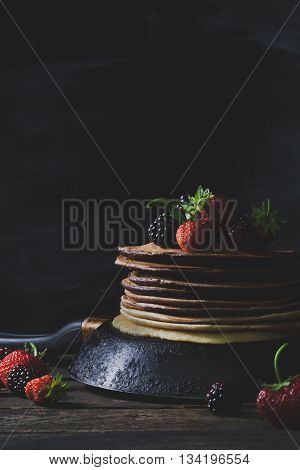 Chocolate pancakes in rusty pan with organic fruits like strawberries and blackberries on old wooden table