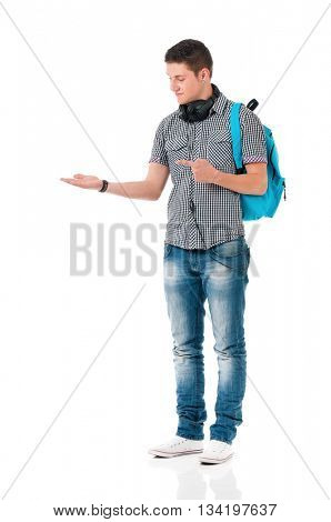Full length portrait of a caucasian guy student of college or university with backpack. Young casual male presenting something on his hand against white background.
