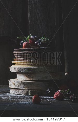 Rustic pancakes with organic fruits on wooden blocks with old wooden doors in backround