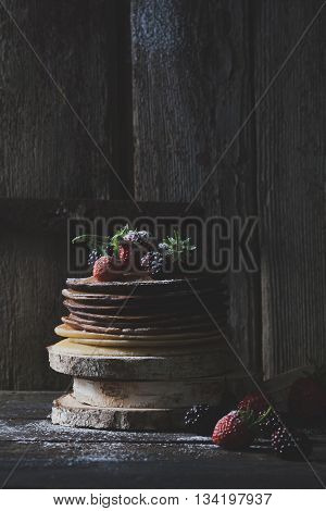 Breakfast in the wood : chocolate pancakes with strawberries blackberries and castor sugar