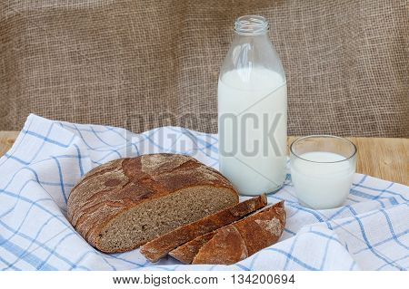 Rye sliced bread with bottle of milk and cup on wooden table