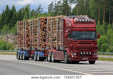 PAIMIO, FINLAND - JUNE 10 2016: Red Scania logging truck hauls pulp wood along freeway. The bioproduct mill of Metsa Group currently under construction will increase the demand of pulp wood.
