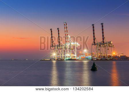 Cargo ship terminal at twilight scene Unloading crane of cargo ship terminal.