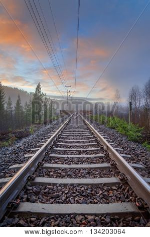 evening mountain landscape with mist and railroad