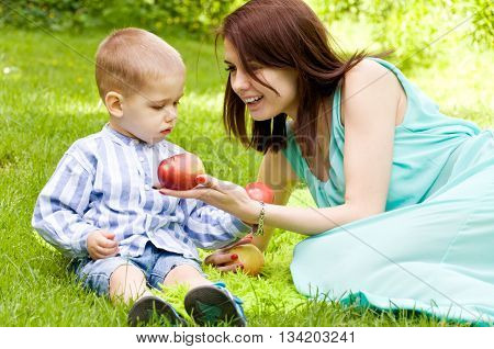 Mother and son spending time in nature. They eat delicious fresh apples
