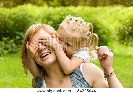 holiday in nature. mother and daughter having fun on the lawn