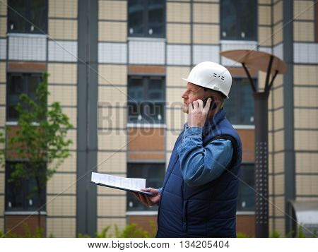 Engineer standing on the background of a new apartment building. House is built. Engineer in a helmet with papers in hand on the phone. The concept of new housing construction, real estate