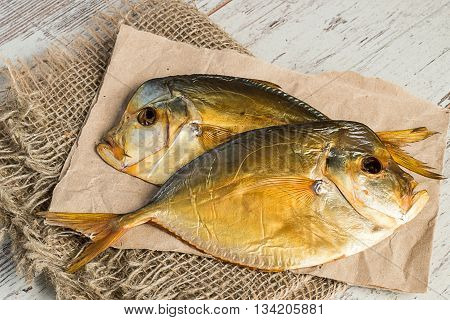 Two smoked fish on a paper on the burlap on a light wooden background.