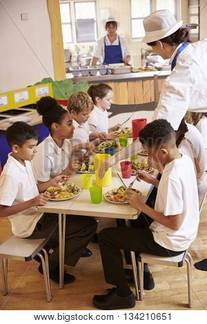 Primary school kids eat lunch in school cafeteria, vertical