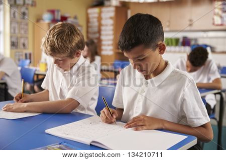 Two schoolboys working in a primary school class, close up