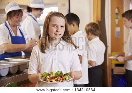 Girl holds a plate of food in school cafeteria, head turned