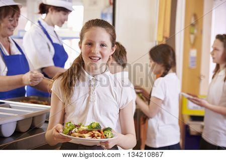 Caucasian schoolgirl holds plate of food in school cafeteria