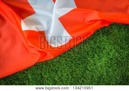 Flags of Switzerland on green grass