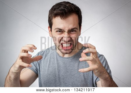 Angry young man clenching his teeth ready to pounce