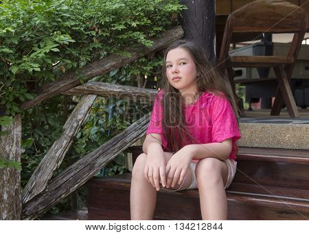Portrait of thinking teenager girl in the garden