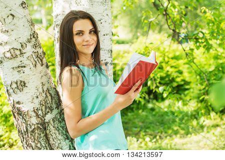 Girl in green park read book in summer sun ligh.