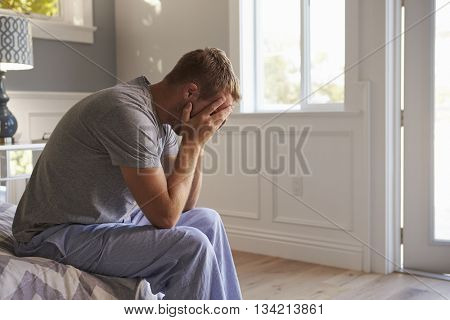 Man Wearing Pajamas Sitting On Bed With Head In Hands