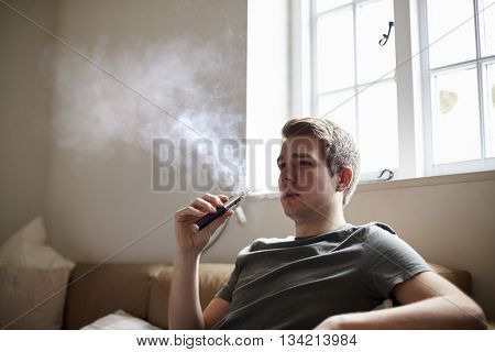 Young Man Using Vapourizer As Smoking Alternative