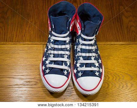 DNIPROPETROVSK, UKRAINE - JUNE 13, 2016: All Star Converse sneakers on wooden background