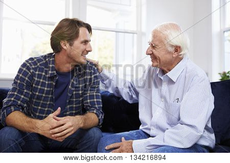 Adult Son Sitting On Sofa And Talking To Father At Home